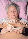 Oude vrouw die in bed liggen Stock Afbeelding