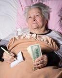 Oude vrouw die in bed liggen Stock Afbeeldingen