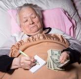 Oude vrouw die in bed liggen Royalty-vrije Stock Afbeeldingen