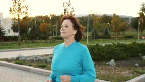 Oude vrouw die bij park lopen stock video