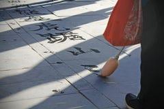Oude vrouw die de Chinese kalligrafie schrijven royalty-vrije stock afbeelding