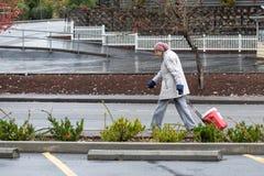 Oude vrouw die in de regen lopen royalty-vrije stock foto