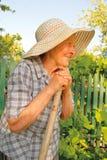 Oude vrouw die in de tuin werkt Stock Foto