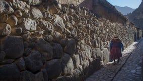 Oude vrouw die door de straten van Ollantaytambo lopen royalty-vrije stock fotografie