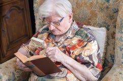 Oude vrouw die een boek lezen Stock Foto's