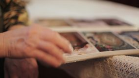 Oude Vrouw die een Foto in Oud Fotoalbum omhoog bekijken, Geheugen, Schuine stand