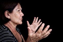 Oude vrouw die en met haar handen spreekt gesturing Stock Afbeeldingen