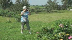 Oude vrouw die foto's nemen de aard van park stock footage