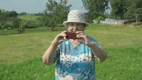 Oude vrouw die foto's nemen de aard van park stock videobeelden