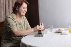 Oude vrouw die giftdoos bekijken die heden goedkeuren royalty-vrije stock foto