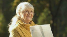 Oude vrouw die goed nieuws in krant over pensioenhervorming lezen, die in park rusten stock video