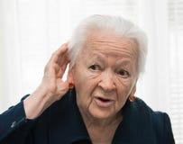 Oude vrouw die hand zetten aan haar oor. Slechte hoorzitting Royalty-vrije Stock Foto's