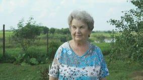 Oude vrouw die in het park van tuin lopen stock video