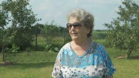 Oude vrouw die in het park van tuin lopen stock videobeelden