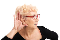 Oude vrouw die iemand afluisteren stock fotografie