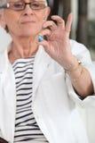 Oude vrouw die medicijn nemen stock fotografie
