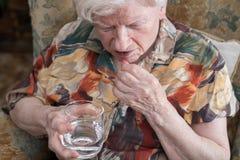Oude vrouw die medicijn nemen Royalty-vrije Stock Foto