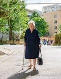 Oude vrouw die met een riet lopen Stock Foto