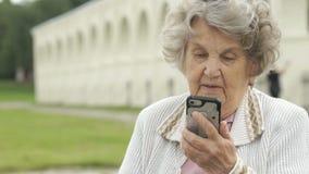 Oude vrouw die met een vriend spreken die een smartphone gebruiken stock footage