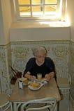 Oude vrouw die ontbijt hebben stock afbeelding