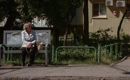 Oude vrouw die op een bus wachten Stock Foto