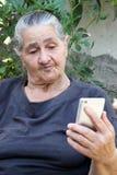 Oude vrouw die op een smartphone kijken royalty-vrije stock afbeeldingen