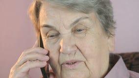 Oude vrouw die op mobiele smartphone ernstig spreken stock videobeelden