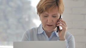 Oude Vrouw die op Telefoon spreken en aan Laptop werken stock video