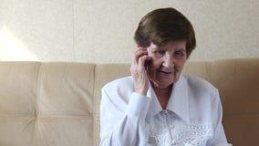 Oude vrouw die op telefoon thuis spreken stock video