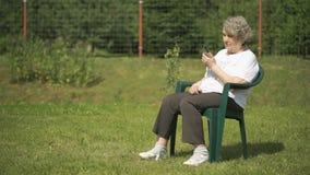 Oude vrouw die in openlucht gebruikend een mobiele telefoon spreken stock videobeelden