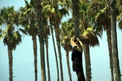 Oude vrouw die over palmen letten op Stock Fotografie