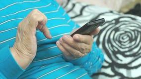 Oude vrouw die smartphone thuis gebruiken stock video