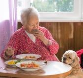 Oude vrouw die soep eten stock afbeelding