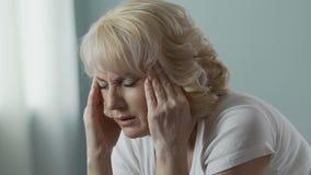 Oude vrouw die tempels wrijven die intens, hoofdpijn, problemen met gezondheid verdelen stock videobeelden