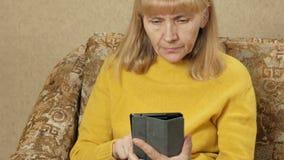 Oude vrouw die thuis op de laag voor Tabletpc rusten Zij doorbladert de pagina's en zorgvuldig gelezen Vakantiehuis stock footage