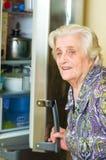 Oude vrouw die voedsel zoekt Stock Foto's