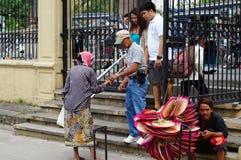 Oude vrouw die voor aalmoes bedelen, die voetganger achtervolgen bij kerkwerf royalty-vrije stock foto's