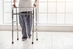 Oude vrouw die vouwbare leurder houden en zich in het ziekenhuis bewegen stock foto's
