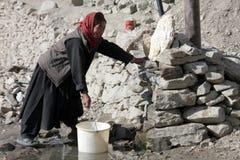 Oude vrouw die water van een put neemt Royalty-vrije Stock Afbeelding