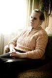 Oude vrouw door het venster Stock Foto