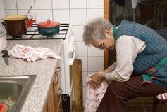Oude vrouw door rust in keuken stock foto's