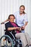 Oude vrouw in een rolstoel en een verpleegster Royalty-vrije Stock Foto