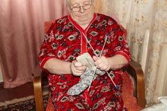 Oude vrouw en breiende kleren Stock Foto's