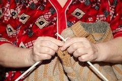 Oude vrouw en breiende sweater Stock Foto's