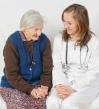 Oude vrouw en de jonge arts Stock Afbeelding