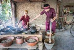 Oude vrouw en jonge man roosterende luwak koffiebonen in Ubud stock foto