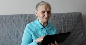 Oude vrouw en tabletpc stock videobeelden
