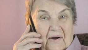 Oude vrouw het glimlachen besprekingen op mobiele telefoon Sluit omhoog stock footage