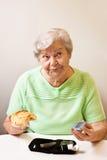Oude vrouw met broodje en bloedglucosemeter Stock Foto