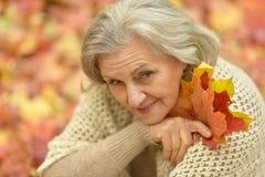 Oude vrouw met de herfstbladeren Stock Foto